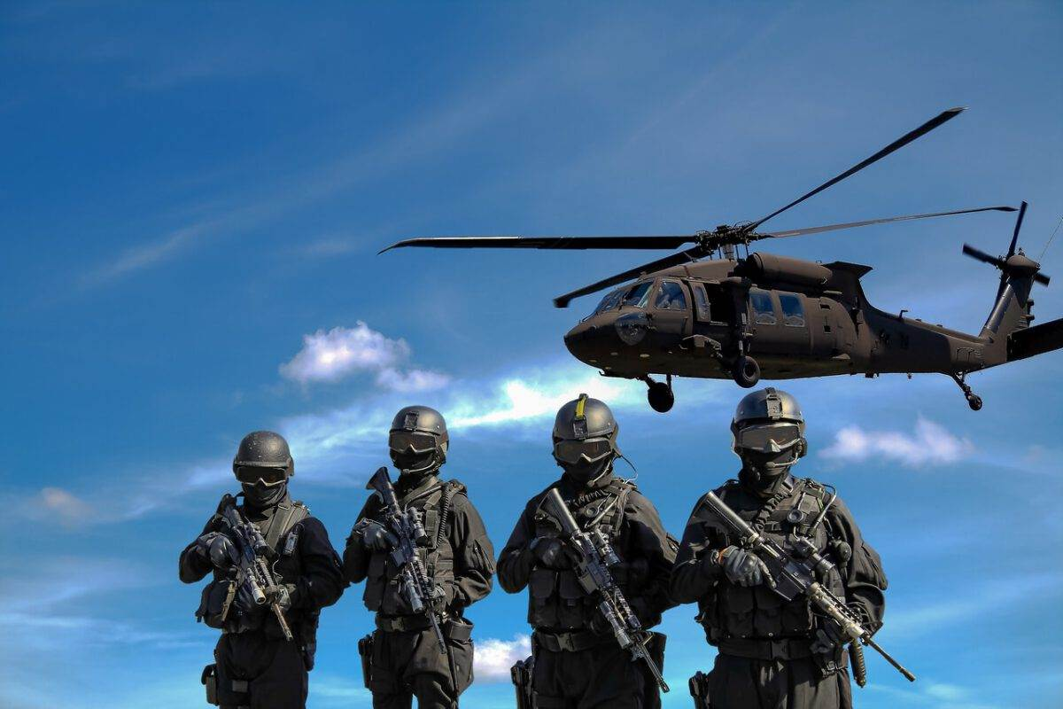 soldiers-holding-guns-below-a-helicopter