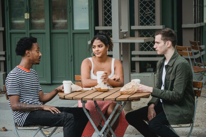Photo-of-three-people-sitting-at-table-outside