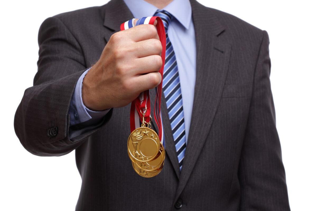 businessman-holding-medal