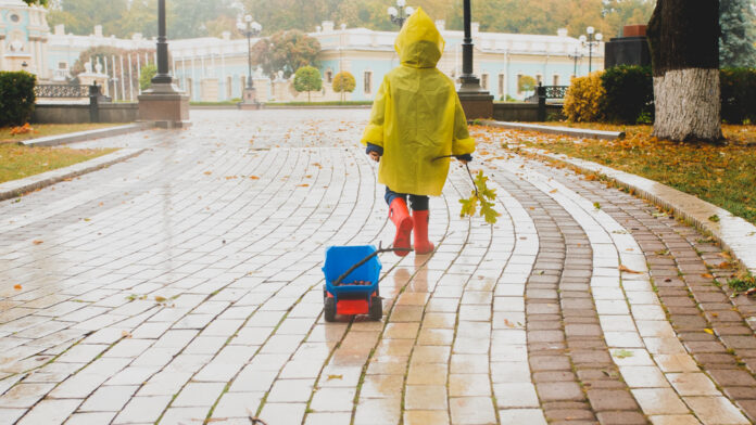 picture-of-a-child-in-rain-jacket-with-autumn-leaves-park