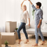 Man And Woman Dancing Among Moving Boxes In New House