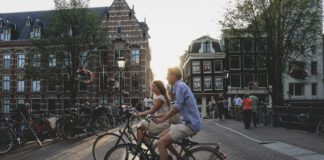 Man-and-woman-cycling-through-Amsterdam-on-summer-evening