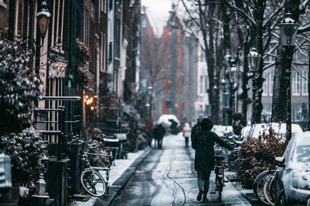 photo-of-woman-walking-bike-along-snowy-dutch-street