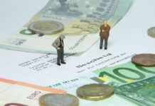 two-minature-men-stand-over-tax-bill-euros