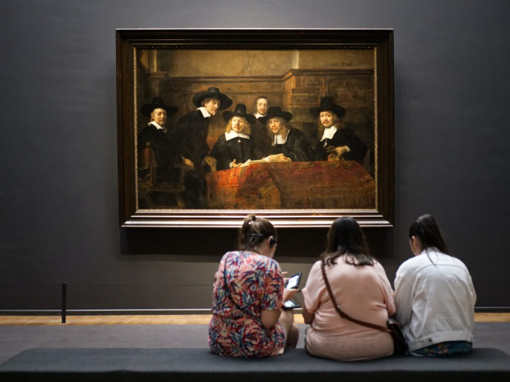 Three girls watching a Rembrandt in the Rijksmuseum, Amsterdam.