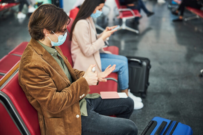 a-picture-of-passengers-waiting-at-an-airport-masked