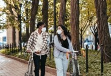 photo-of-two-girls-walking-with-bikes-and-face-masks