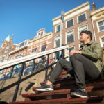 Urban asian man with backpack sitting on stairs. Good looking. C