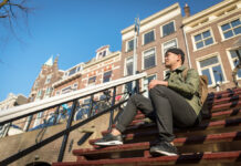 young-man-sitting-on-steps-to-amsterdam-rental-apartment