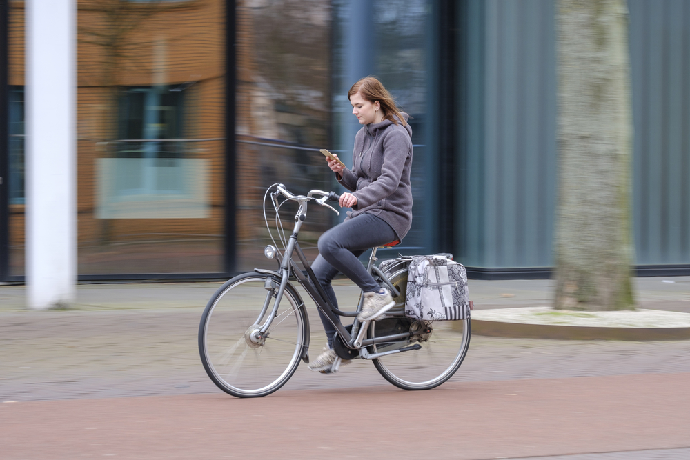 girl-using-her-phone-while-cycling-in-the-netherlands