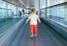 Child-walking-on-walkway-in-airport