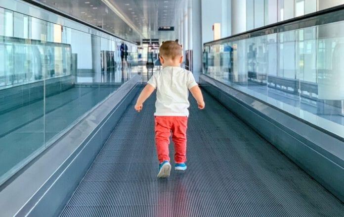 Child-walking-on-walkway-in-airport
