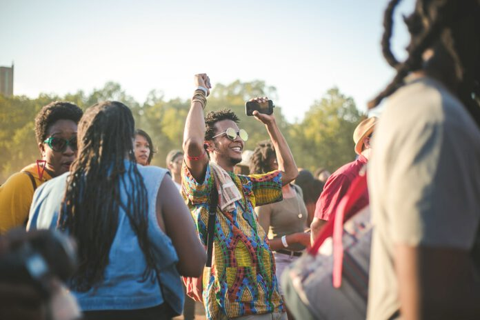 photo-young-man-dancing-at-outdoor-festival-with-small-crowd