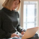woman-in-gray-sweater-sitting-on-wooden-floor-typing-on-3759115
