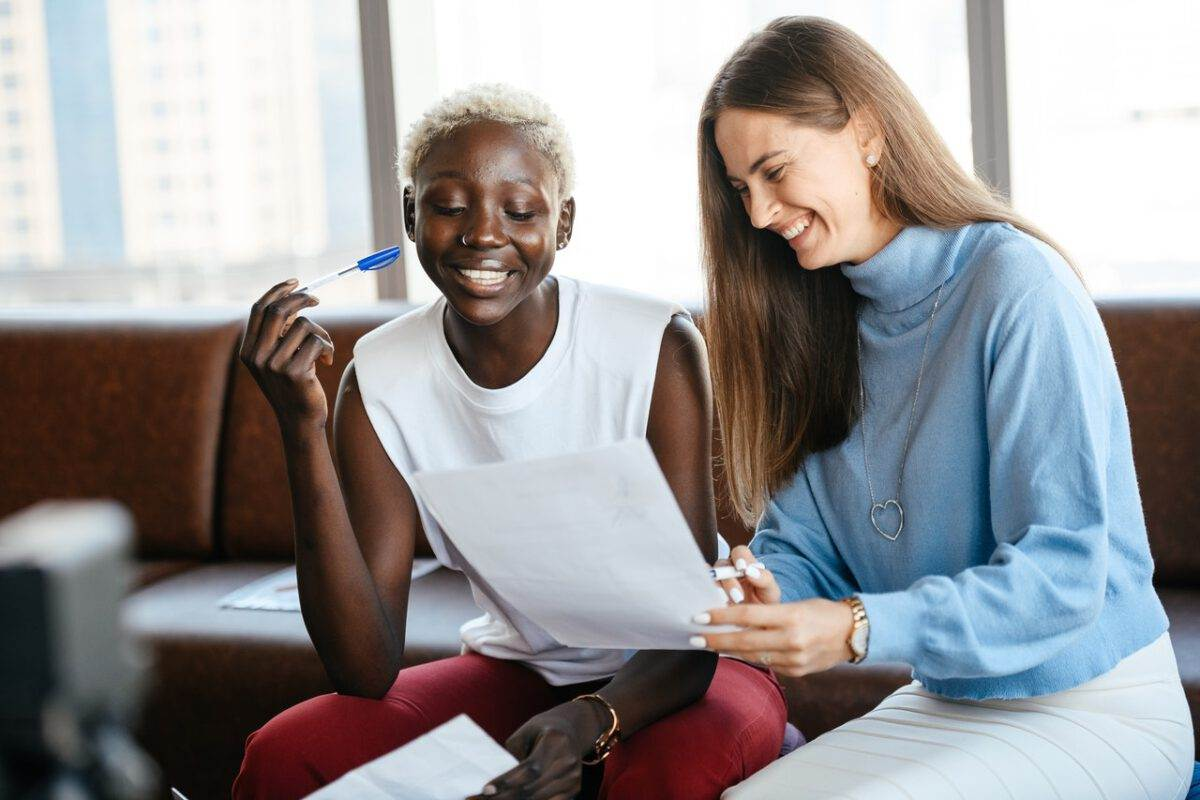photo-of-woman-signing-work-contract-helped-by-colleague-to-understand