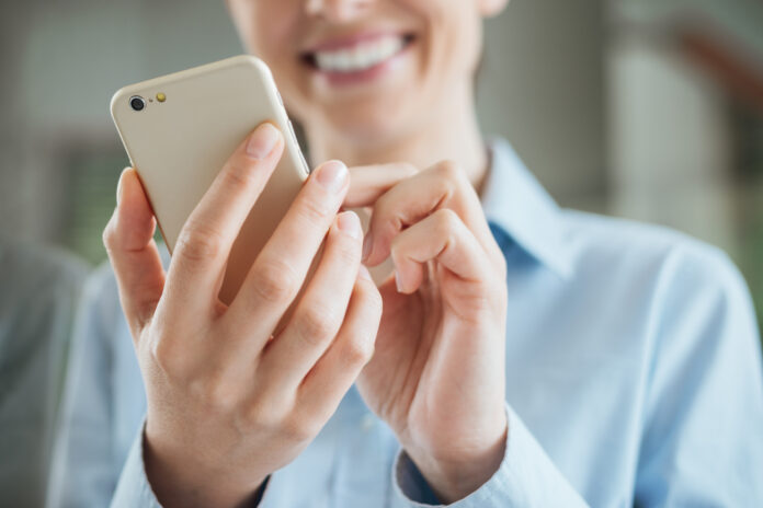 woman-smiling-using-her-phone