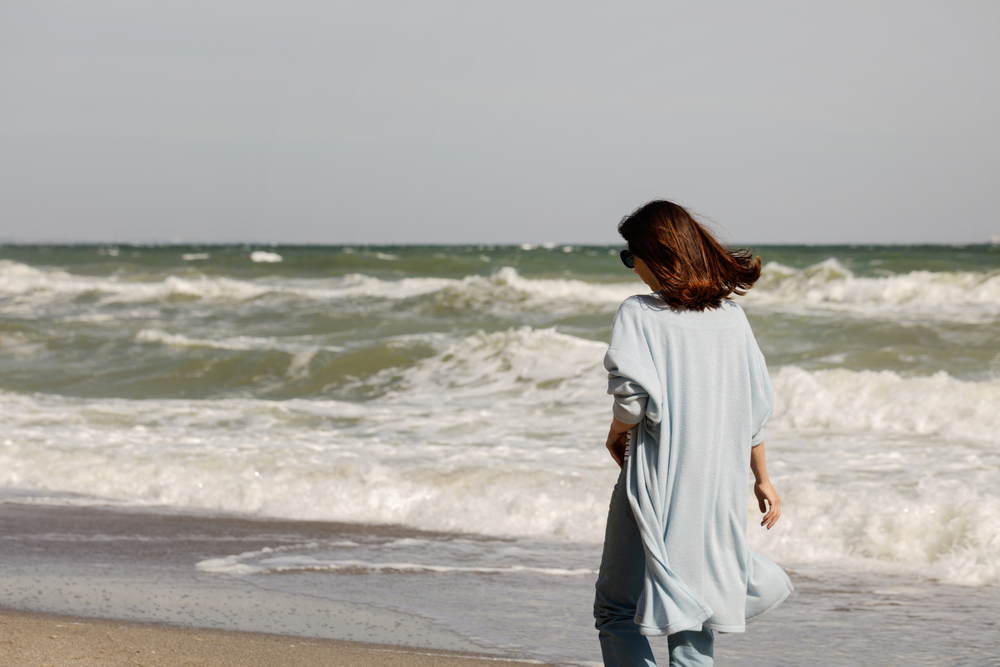 picture-of-woman-walking-on-a-windy-beach