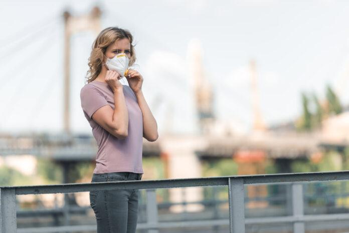 photo-of-woman-wearing-covid-mask-on-bridge