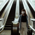 woman-with-a-face-mask-going-down-an-escalator-4429654