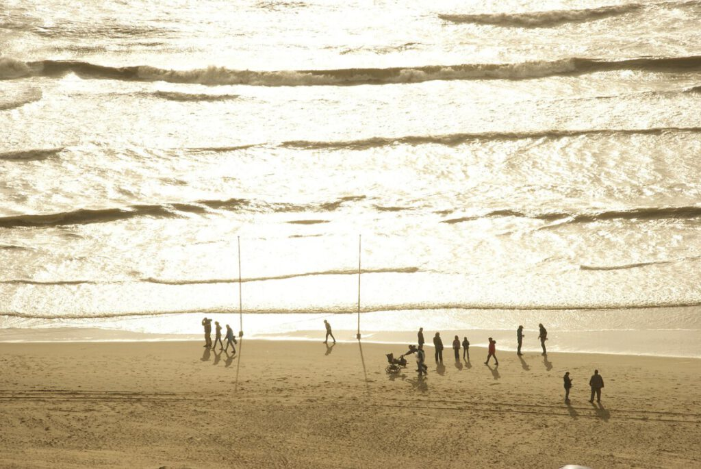 photo-from-above-of-people-walking-on-zandvoort-beach-netherlands-at-sunset