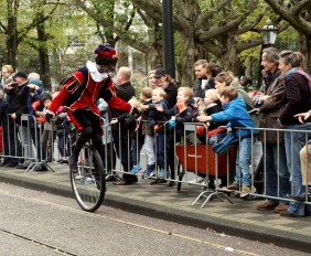 Zwarte Piet riding a unicycle in a parade in Amterstam