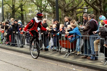 Zwarte Piet riding a unicycle in a parade in Amterstam